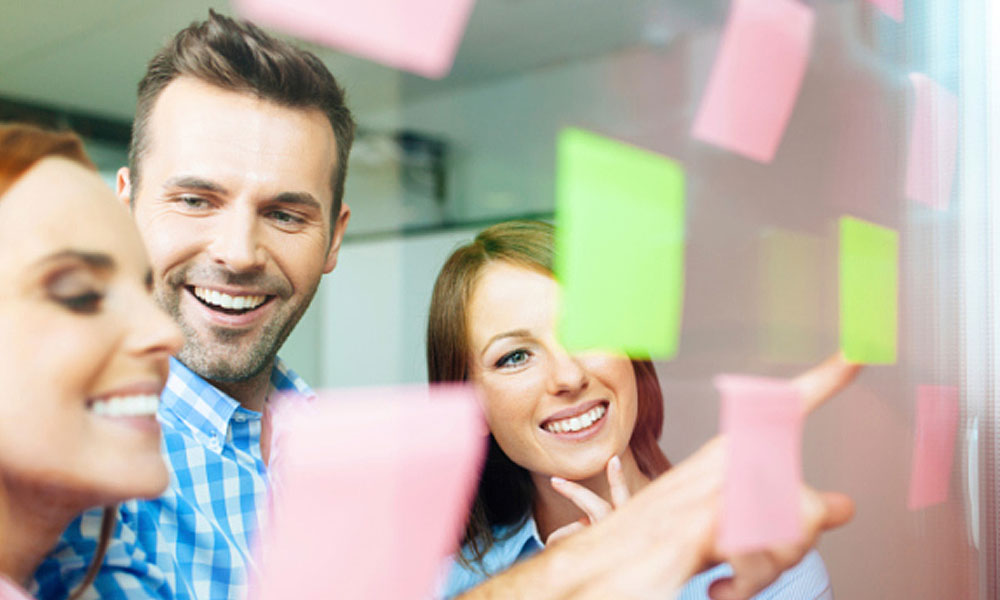5 important ways to maximize employee engagement - three people looking at a board with sticky notes
