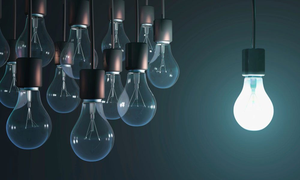 5 qualities successful businesses have in common - group of light bulbs with 1 lite.