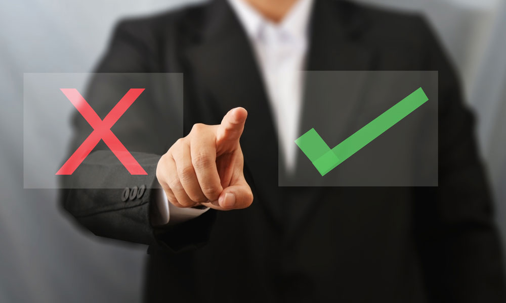 7 mistakes to avoid when starting a business - man pointing to a screen with an X and check mark