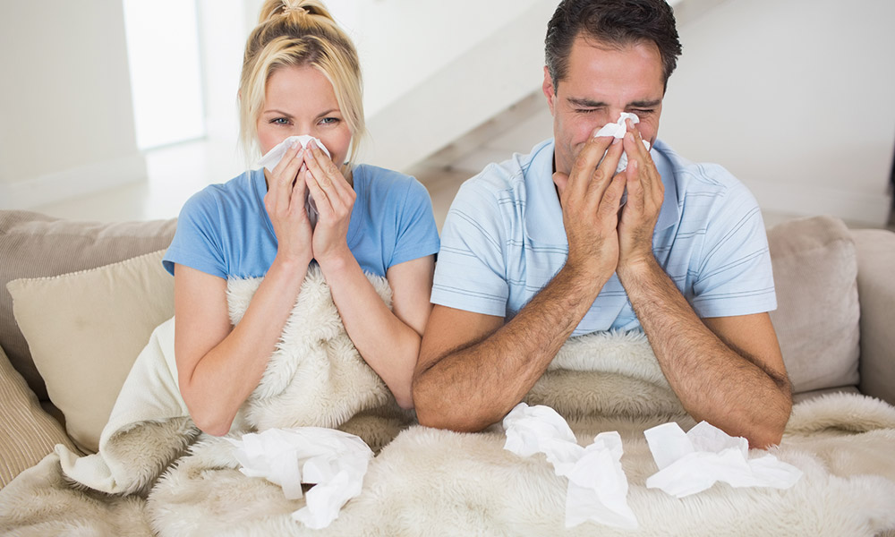 California sick leave - man and woman on the couch blowing their nose