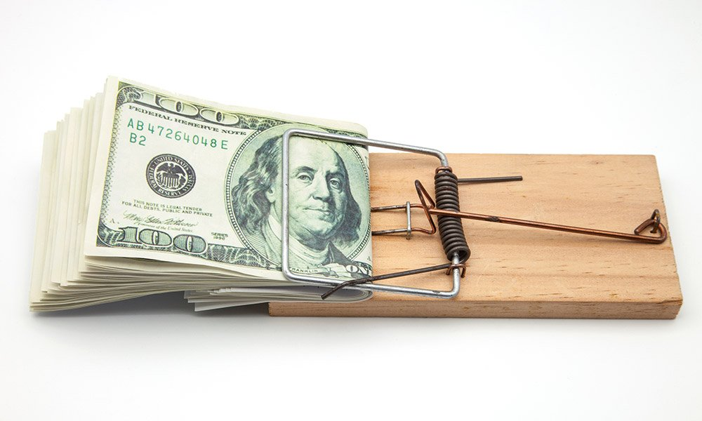 common small business payroll pitfalls - folded 100 dollar bills in a mouse trap