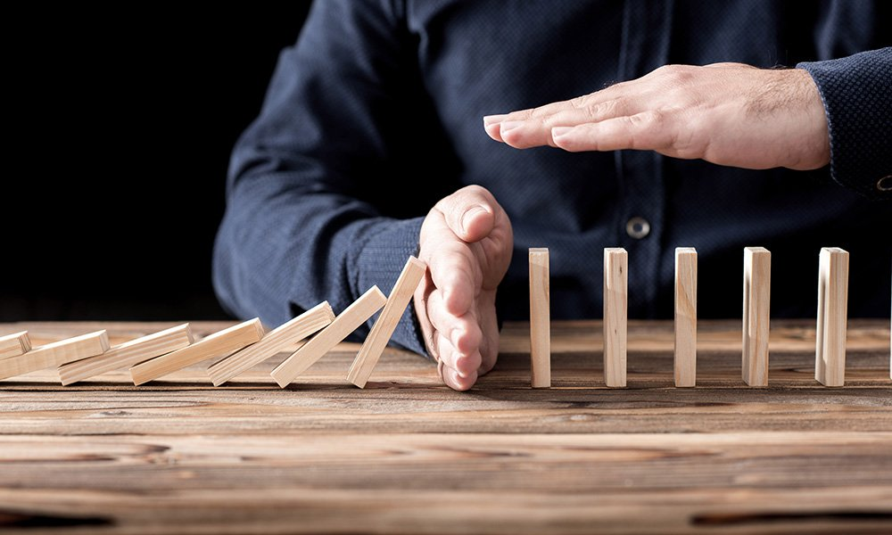 Credit.com How to prevent your small business - row of dominoes fall with a hand in the middle stopping them