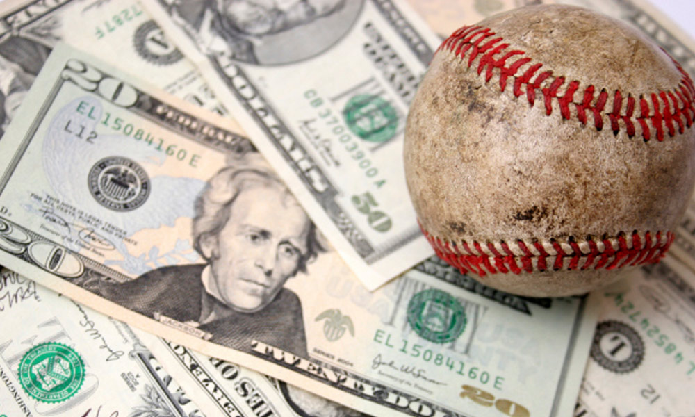 did income tax rate help cubs sign lester - a baseball on top of a variety of dollar bills