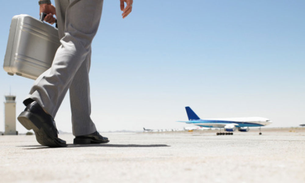 do employees get paid travel time - Man holding a brief case walking towards a plane