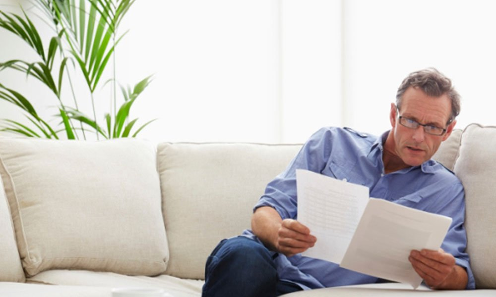 do i pay corporate or personal taxes - guy on couch looking at tax forms