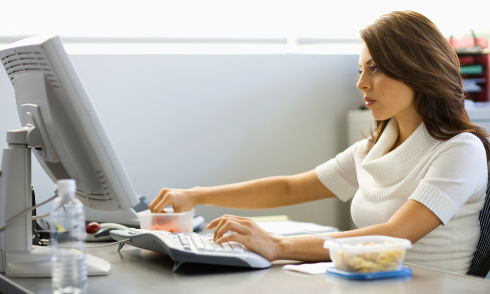 eat at your desk - woman sitting in front of a computer with lunch in a Tupperware container
