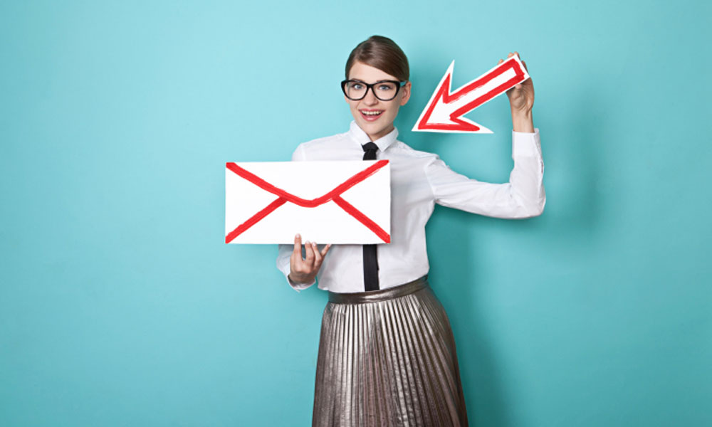 gmail plugins for productivity - woman holding a large envelope in her left hand with a large arrow in her right pointing at the envelope.