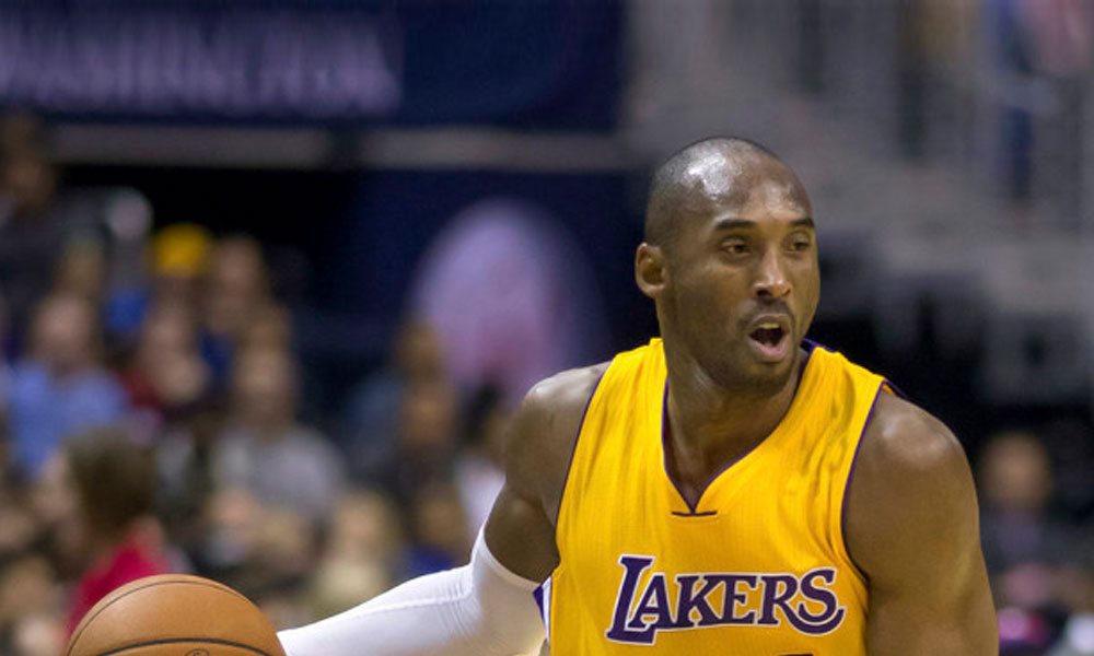 highest paid NBA players - Kobe Byrant in a yellow lakers jersey
