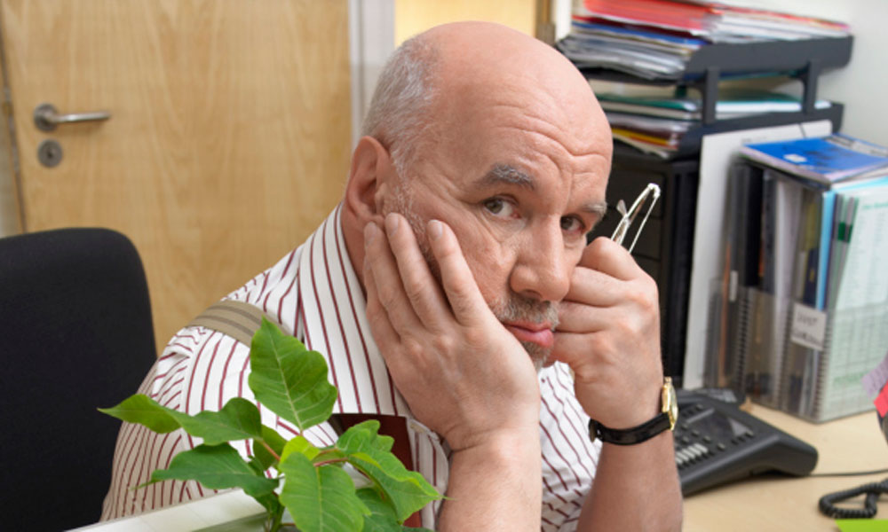 how to fire someone before the holidays - older balding man sitting at a desk looking distraught