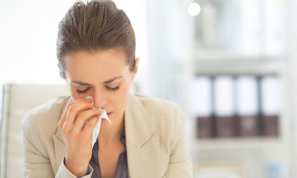 how to keep your office healthy - employee sitting at desk blowing nose