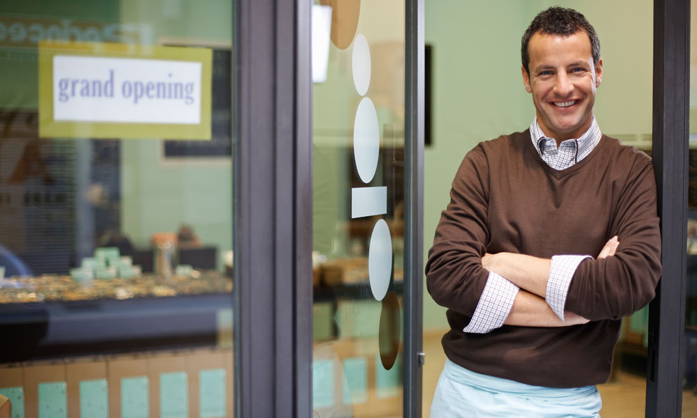 How to open a small restaurant - restaurant owner standing next to a grand opening sign.
