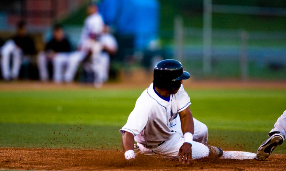 how to save on your fantasy baseball payroll - baseball player sliding into a base.