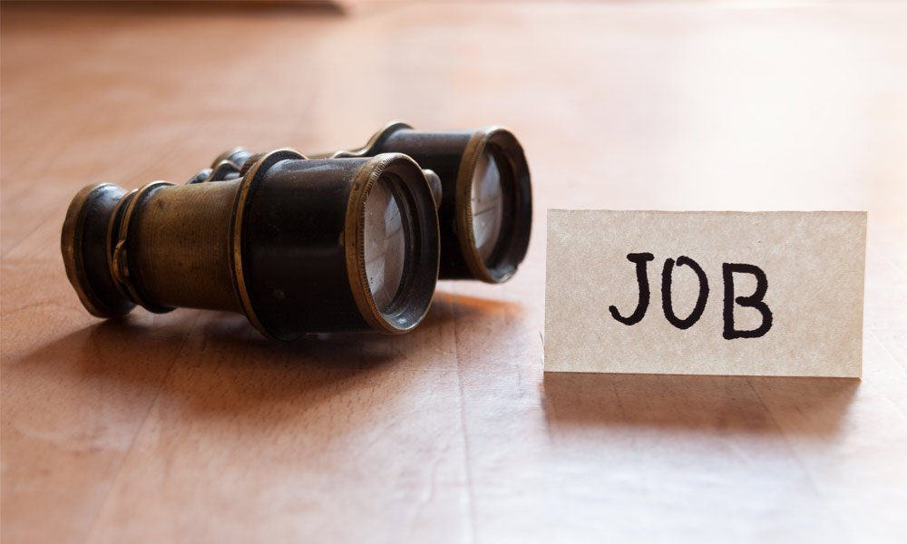 job seekers know what they want - binoculars on a table with a job sign