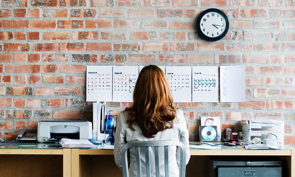 most common payroll mistakes new companies - business owner looking at calendar on the wall