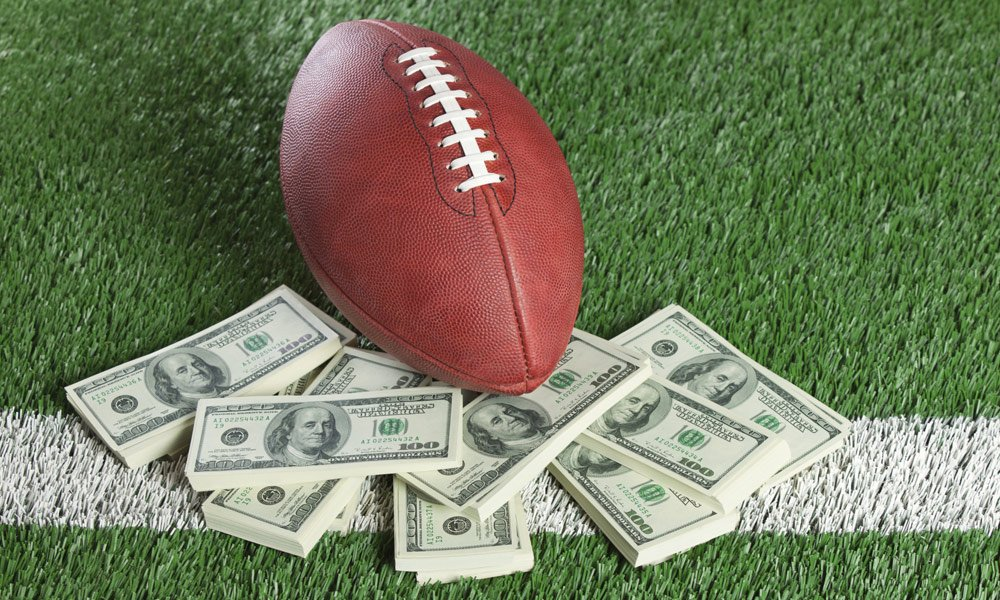 NFL playoff team salary caps - football on a football field with stacks of $100 bills