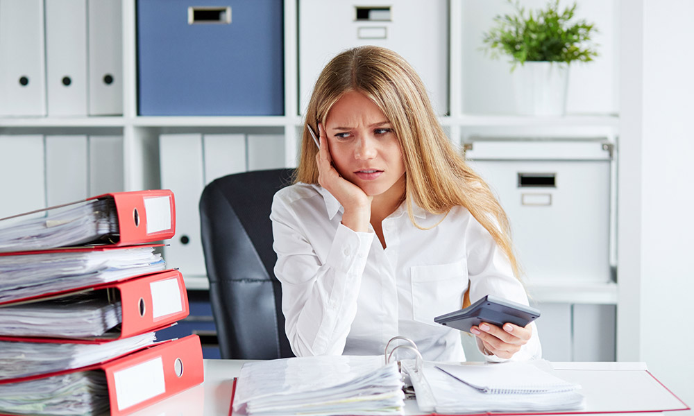 switching payroll services - woman behind a desk with a stack of paperwork looking dismayed