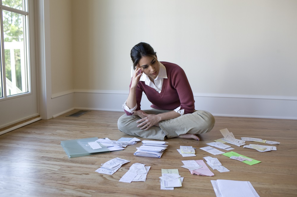 what to do part three - woman sitting on wood floor organizing bills