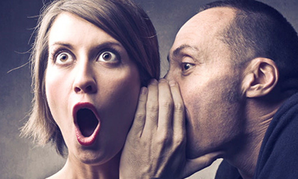 workplace solutions to avoid gossip - man whispering into woman's ear and the woman looks shocked