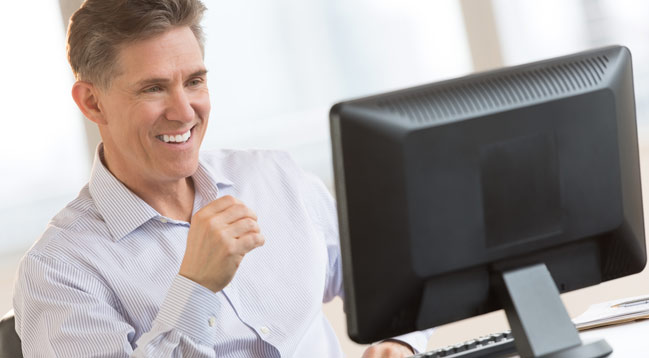An older smaller business gentleman smiling at his computer screen due to the ease of our services.